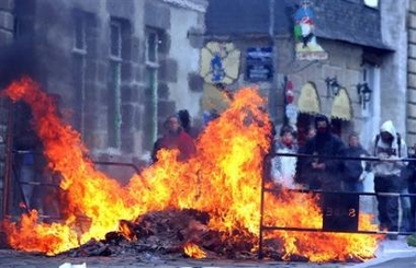 Photo: Youths stand behind a fire after a demonstration in Rennes, western France, Tuesday, April 4, 2006. Hundreds of thousands of protesters marched through cities around France, hoping to make their biggest show of strength yet to demand the repeal of a job law that has divided the country, known as CPE, and which would make it easier for employers to fire young workers.(AP Photo / Vincent Michel)