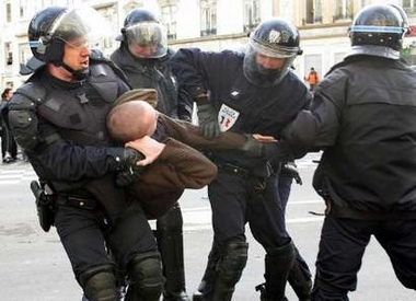 Photo: Riot police arrest a protestor following clashes between an element of violent demonstrators and police after a student demonstration against the First Job Contract (CPE) in Lille, northern France, April 4, 2006. French transport workers and teachers staged new strikes on Tuesday and students across the country gathered for street protests they hope will kill off the disputed CPE, a youth hire-and-fire law. ATTENTION EDITORS - French law requires that the faces of law enforcement officers are masked in publications within France. REUTERS/Jean-Pierre Rafto