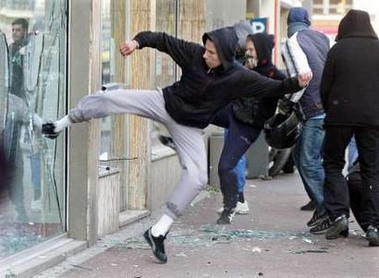Photo: Protestors smash shop windows during a student demonstration against the First Job Contract (CPE) in Lille, northern France, April 4, 2006. French transport workers and teachers staged new strikes on Tuesday and students across the country gathered for street protests they hope will kill off the disputed CPE, a youth hire-and-fire law. REUTERS/Jean-Pierre Rafto
