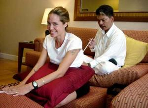 U.S. actress Angelina Jolie smiles while getting a tattoo of a tiger from Thai artist Sompong Kanphai during her visit to Bangkok on July 8, 2004. Jolie was in Thailand after her visit to Cambodia. Picture taken July 8, 2004. THAILAND OUT NO SALES NO ARCHIVES REUTERS/Nation