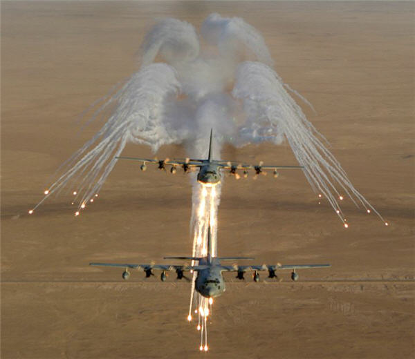 Aerial Photography of Two United States Marine Corps KC-130 Hercules Aircraft, Assigned to Marine Aerial Refueler-Transport Squadron Two Thirty Four (VMGR-234), Firing Flares That Are Used for Protection Against an Attack by Surface-to-Air Missiles During Operation Iraqi Freedom, September 4, 2003 Al Jumhuriyah al Iraqiyah — Republic of Iraq