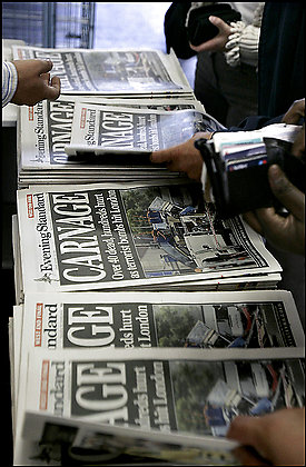 A London tabloid proclaiming 'Carnage' about attacks on British trains is snapped up by commuters. 'Both the media and terrorists benefit from terrorist incidents,' concludes a recent study. The terrorists get publicity and the media gain circulation and profits. Photo Credit: By Matt Dunham -- Associated Press