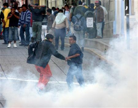 Teacher Strike Sparks Violence in Oaxaca, Mexico Photo 3 Striking teachers run away from tear gas during violent clashes with state riot police during a protest in Oaxaca's main square about 188 miles southwest of Mexico City June 14, 2006. REUTERS/Jorge Luis Plata