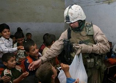 Staff Sergeant Raymond Plouhar This photo released by the U.S. Marine Corps shows Staff Sgt. Raymond Plouhar handing candy to students at the Al Nabatiya Elementary School, May 9, 2006, near Fallujah, Iraq. Plouhar, 30, of Lake Orion, Mich., who was featured in Michael Moore's antiwar documentary, 'Fahrenheit 9/11,' was killed on June 26, 2006, by a roadside bomb in Anbar province in his second tour of duty in Iraq. (AP Photo/U.S. Marine Corps)