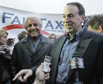 Mike Huckabee - False Conservative? Republican presidential hopeful, former Arkansas Gov. Mike Huckabee, right, talks with reporters as Rick Flair campaigns outside Williams Brice Stadium before the Clemson-South Carolina football game Saturday, Nov. 24, 2007, in Columbia, S.C. (AP Photo/Mary Ann Chastain)