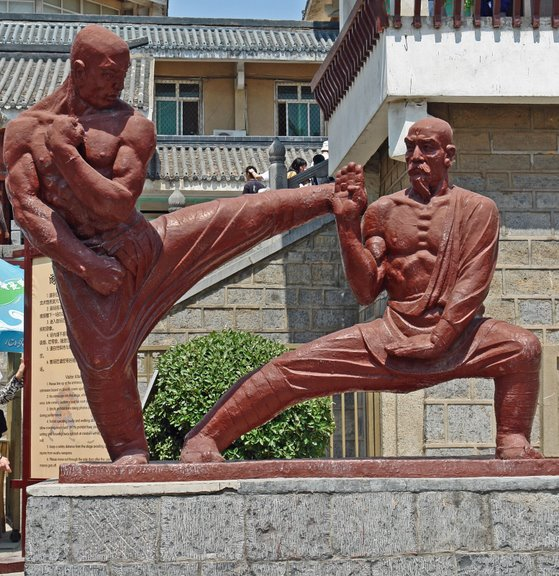 Shaolin Monks Bow Out of Kung Fu Tournament China.Henan Province.Shaolinsi.Shaolin Temple: Statue of Monks Practicing Kung Fu