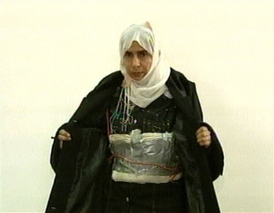 Al Qaeda Unfair to Women! In this file image made from television on Nov. 13, 2005, Iraqi Sajida al-Rishawi opens her jacket and shows an explosive belt as she confesses on Jordanian state-run television to her failed bid to set off an explosives belt inside one of the three Amman hotels targeted by al-Qaida. Women Muslim extremists have posted Internet messages in recent weeks expressing frustration with the al-Qaida No. 2 leader's refusal to give them a larger role in terror attacks - an extraordinary, emotional debate that offers rare insight into the tense gender politics lurking below the surface of al-Qaida's severe strain of Islam. (AP Photo/Jordanian TV, File)
