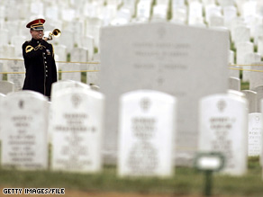 U.S. Army bugler plays taps during burial services for a female soldier at Arlington National Cemetery in 2005.