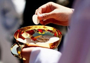 WASHINGTON - APRIL 17:  A priest holds a Holy Communion wafer as Pope Benedict XVI celebrates Mass at Nationals Park April 17, 2008 in Washington, DC. Today is Pope Benedict XVI\'s third day of his visit to the United States.  (Photo by Win McNamee/Getty Images)