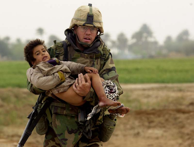 Pfc. Joe Dwyer carried a young Iraqi boy who was injured during a heavy battle between the U.S. Army\'s 7th Cavalry Regiment and Iraqi forces near the village of Al Faysaliyah, Iraq, on March 25, 2003. Dwyer died of an apparent overdose at his home in North Carolina on June 29, 2008.