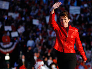 Sarah Palin, in a red leather jacket, waves as she steps on stage before a crowd at a baseball field in Grand Junction, Colo., on Monday.