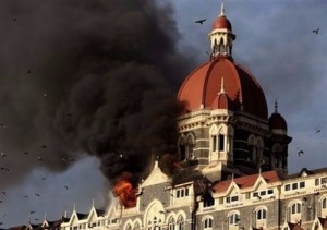 Flames and smoke gush out of the historic Taj Mahal Hotel in Mumbai.Indian army commandos were Thursday battling heavily-armed Islamist gunmen who launched coordinated attacks against luxury hotels and other targets in Mumbai, killing at least 100 people. (AFP/Indranil Mukherjee)