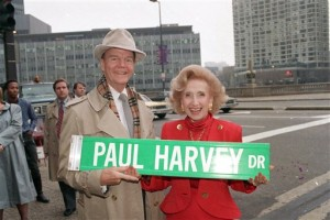 In this Nov. 16, 1988 file photo, radio commentator Paul Harvey and his wife, Lynne, hold a street sign bearing his name in Chicago. A one-block stretch of East Wacker Dr. is changed to Paul Harvey Dr. in honor of the well-known broadcaster. ABC Radio Network says broadcasting pioneer Paul Harvey has died at the age of 90. Network spokesman Louis Adams says Harvey died Saturday Feb. 28, 2009 at his winter home in Phoenix, surrounded by family.  (AP Photo/Charles Bennett, File)