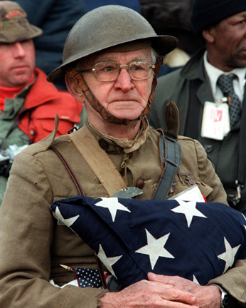 Joseph Ambrose, an 86-year-old World War I veteran, attends the dedication day parade for the Vietnam Veterans Memorial in 1982, holding the flag that covered the casket of his son, who had been killed in the Korean War.