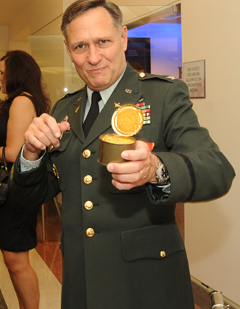 Col. Henry A. Moak Jr. digs in to an Army ration pound cake from 1973 at his retirement party. (Staff Sgt. Sun Vega/U.S. Army)