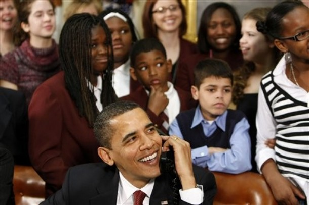 President Barack Obama, accompanied by members of Congress and school children, talks to astronauts on the International Space Station, Tuesday, March 24, 2009, from the Roosevelt Room of the White House in Washington.