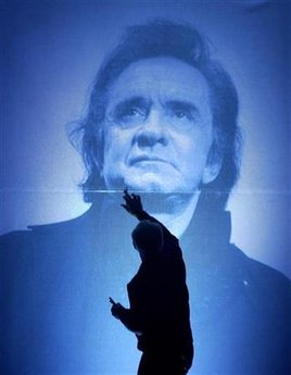 A stage hand at the Ryman Auditorium puts the final touchs on a large photo of the late country music legend Johnny Cash, before the Cash tribute concert in Nashville, Tennessee, late November 10, 2003. REUTERS/John Sommers II JPSII/GN