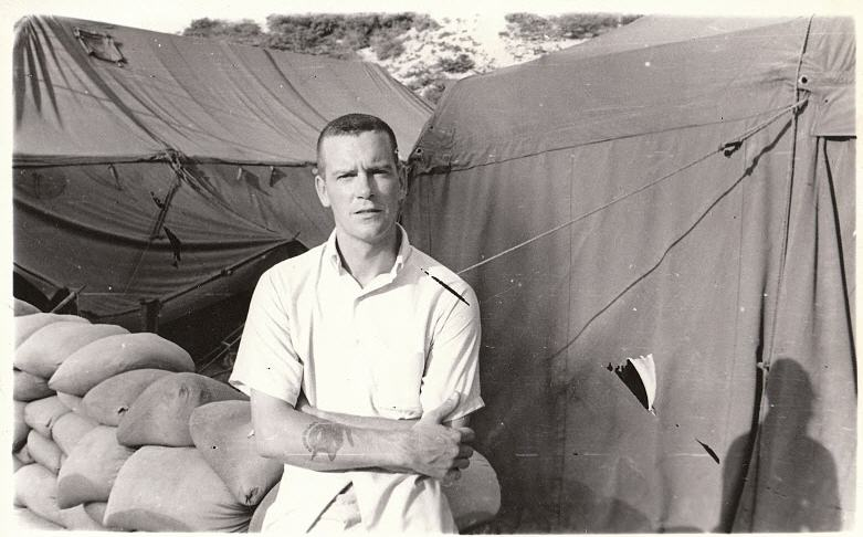 Dad in a high-and-tight haircut but wearing Mufti for some reason.  Again, I'd guess Vietnam from the age and surroundings.