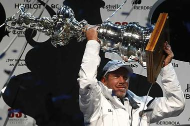 BMW Oracle owner Larry Ellison lifts up the trophy after winning the 33rd America's Cup in Valencia, Sunday.  Heino Kalis / Reuters