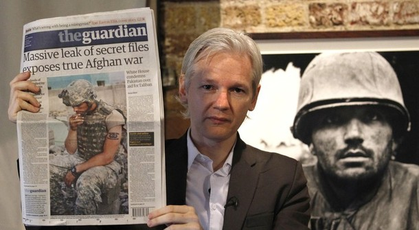 Wikileaks founder Julian Assange holds up a copy of the Guardian newspaper during a press conference at the Frontline Club in central London
