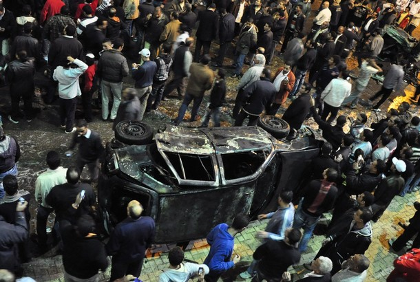 Onlookers gather around a damaged car after a bomb exploded in Alexandria