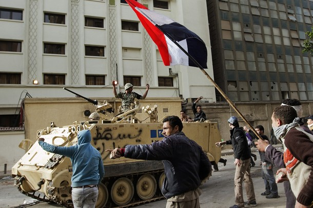 Egyptian protesters run past an army arm