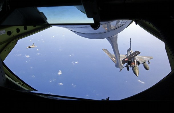 A French  Mirage 2000 fighter jet, accompanied by a French Rafale, refuels with an airborne Boeing C-135 refuelling tanker aircraft above the Mediterranean Sea