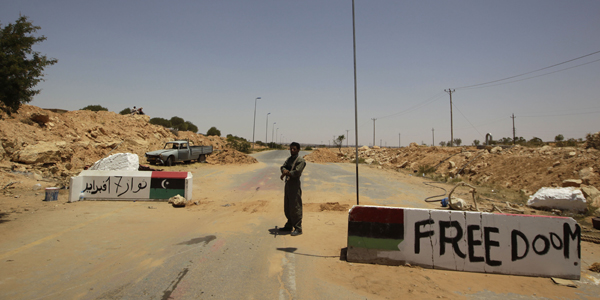 A rebel fighter guards a checkpoint while civilians flee fighting in Al-Qawalish in the western mountains of Libya