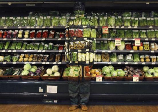 Artist Liu Bolin demonstrates an art installation by blending in with vegetables displayed on the shelves at a supermarket in Beijing