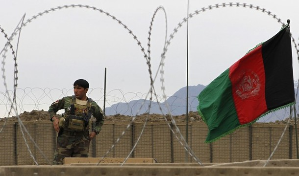 Afghan National Army soldier stands near Afghan national flag in Kunar province