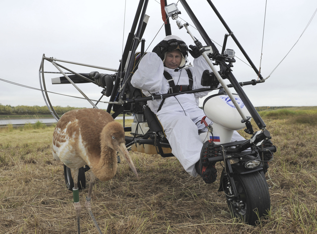 Russian President Vladimir Putin sits in a motorised deltaplane near a crane at Yamalo-Nenets district