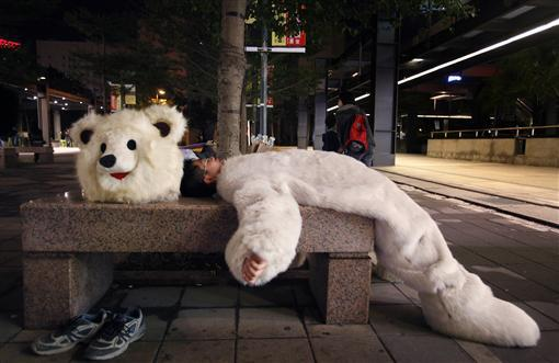 An environmentalist dressed as a polar bear rests after a candlelight vigil to raise awareness of climate change in Taipei