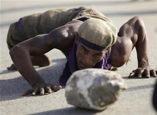 A Cuban sackcloth-dressed worshipper crawls as he pushes a rock to pay homage along a road leading to the shrine of Saint Lazarus in the town of Rincon near Havana