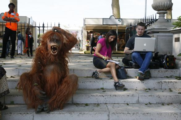 A man dressed as an orangutan sits next to members of the press during media day at the Chelsea Flower Show in London