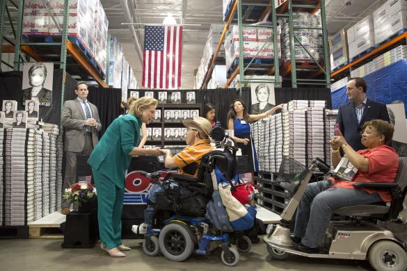 "Former U.S. Secretary of State Hillary Clinton greets people as she signs copies of her book ""Hard Choices"" at a Costco store in Arlington, Virginia"