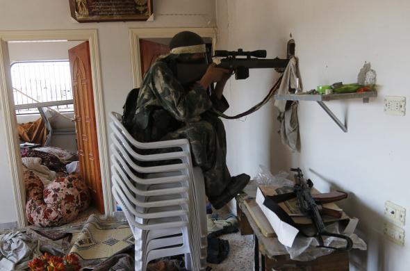 A rebel fighter sits on chairs as he aims his weapon through a hole inside a house in the town of Morek in Hama province