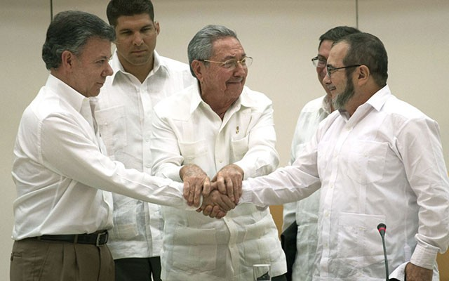 Cuban-President-Raul-Castro-C-encourages-President-Santos-L-and-Timochenko-to-shake-hands-640x400
