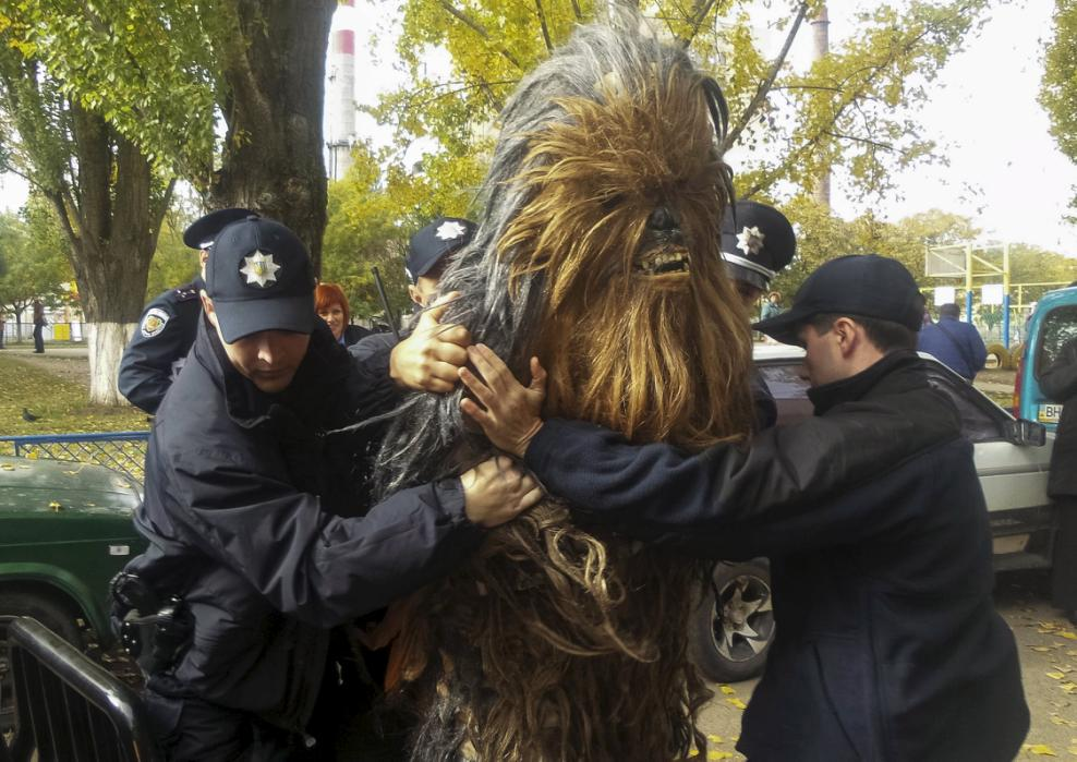 Policemen detain a person dressed as Star Wars character Chewbacca during a regional election near a polling station in Odessa, Ukraine, October 25, 2015. Ukrainians go to the polls on Sunday to appoint mayors and council heads to regional seats. The person was detained for illegal election-day campaigning, according to local media. REUTERS/Ihor Babak      TPX IMAGES OF THE DAY