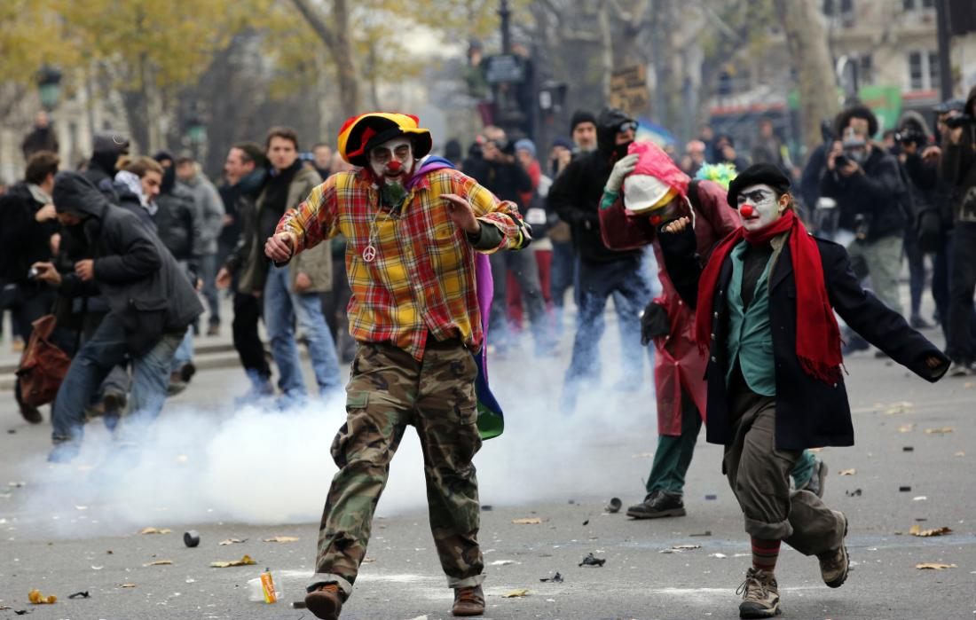 Activists run as they clash with policemen during a protest ahead of the 2015 Paris Climate Conference, in Paris, Sunday, Nov. 29, 2015. More than 140 world leaders are gathering around Paris for high-stakes climate talks that start Monday, and activists are holding marches and protests around the world to urge them to reach a strong agreement to slow global warming. (AP Photo/Christophe Ena)