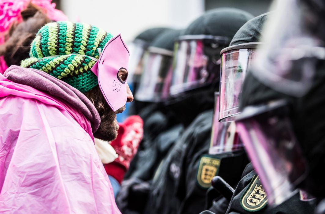 An activist  in pink clothes and a mask clashes with riot police during a demonstration organized to protest against the Federal Congress held by far-right NPD on Nov. 21, 2015 in Weinheim, Germany. (Simon Hofmann/Getty Images)