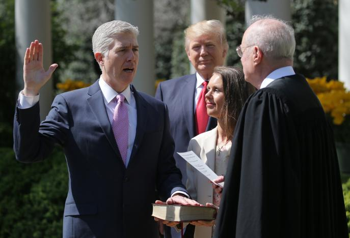 Judge Gorsuch is sworn in by Supreme Court Associate Justice Kennedy as U.S. President Trump watches in the Rose Garden of the White House in Washington